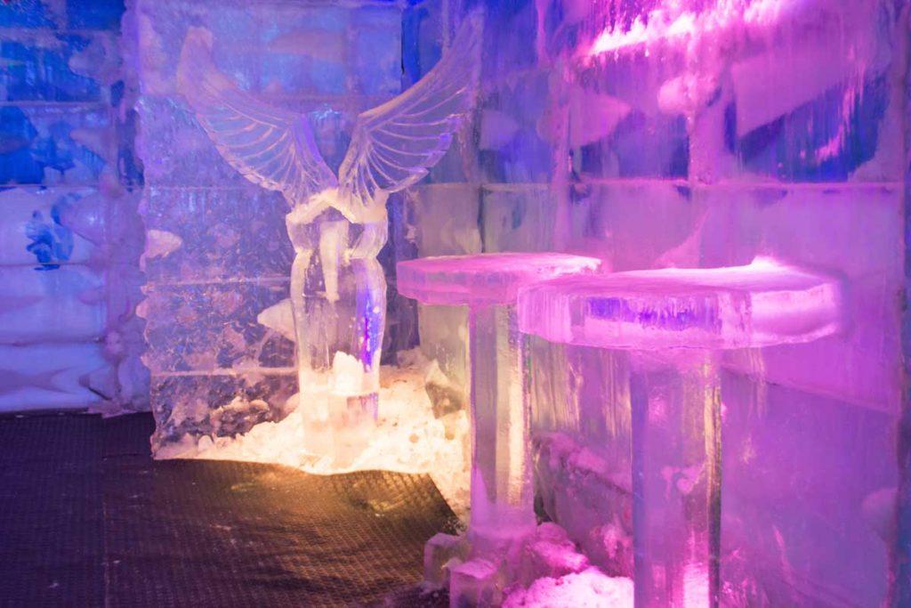 Em primeiro plano duas mesas de gelo e ao fundo a escultura de asas de gelo. É possível ver também as paredes congeladas do bar.