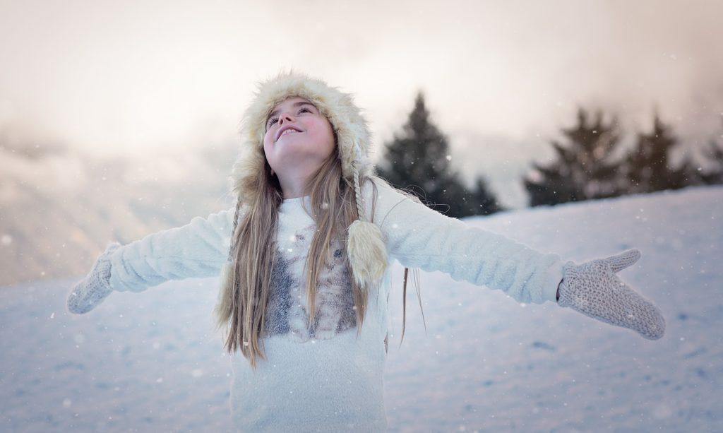 Menina olhando para o céu de braços abertos a espera dos flocos de neve que caem sobre ela. Ela está de luvas, gorro e casaco apropriados para a neve.