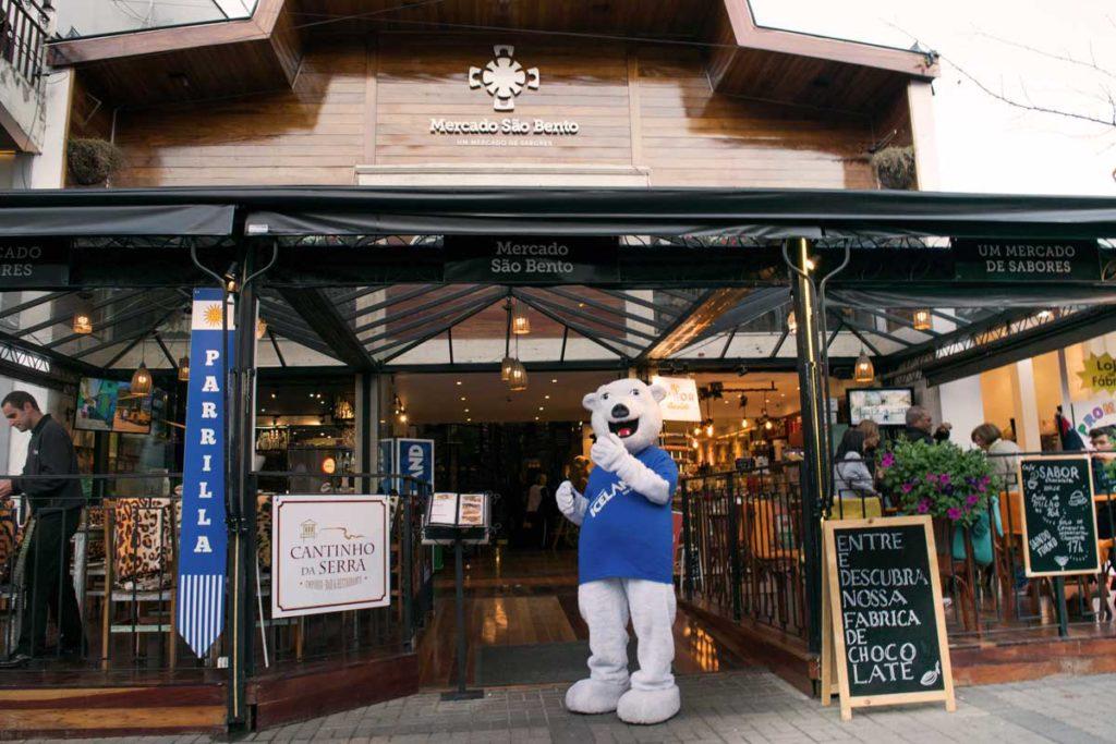 O mascote Ursão em frente do Mercado São Bento, onde fica o Iceland, acenando aos visitantes.