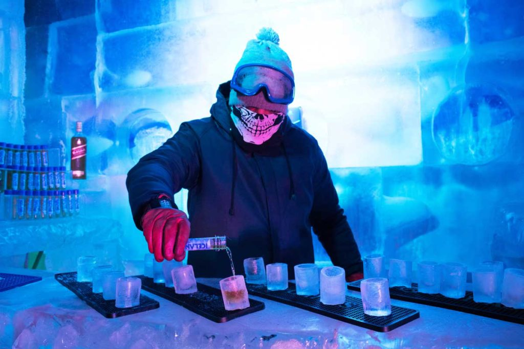 Barman servindo doses nos copos de gelo.