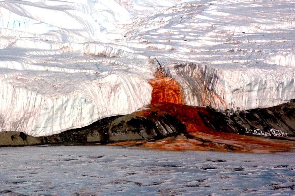 Cascata de óxido de ferro que possui uma queda avermelhada em meio às geleiras.